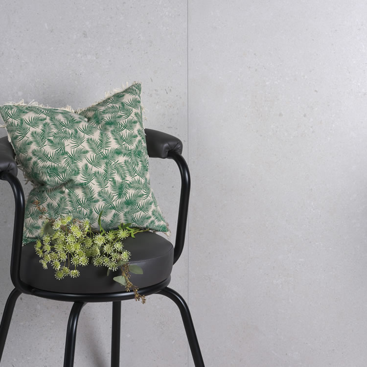 Photo of the Ca' Pietra Hampshire Porcelain Matt Tile in Perla with a black chair and green cushion