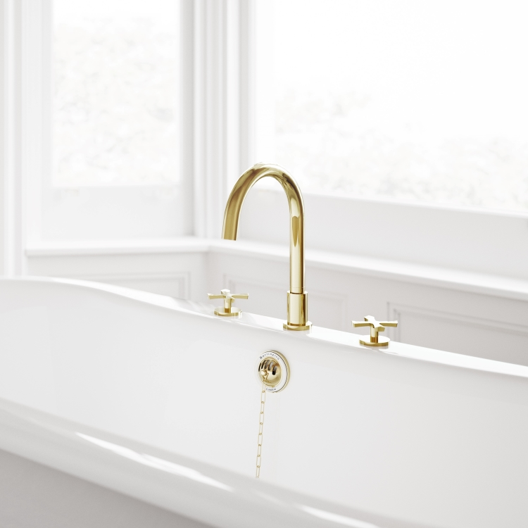 Image close-up of Burlington Riviera 3 Tap Hole Bath Mixer Set in Gold mounted on bath in white bathroom with windows behind