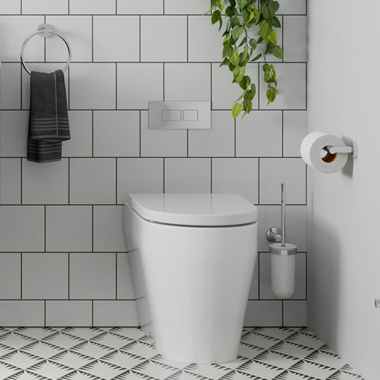 Photo of the Hoxton Toilet Brush Holder with the Hoxton toilet, other chrome accessories and white tiled wall
